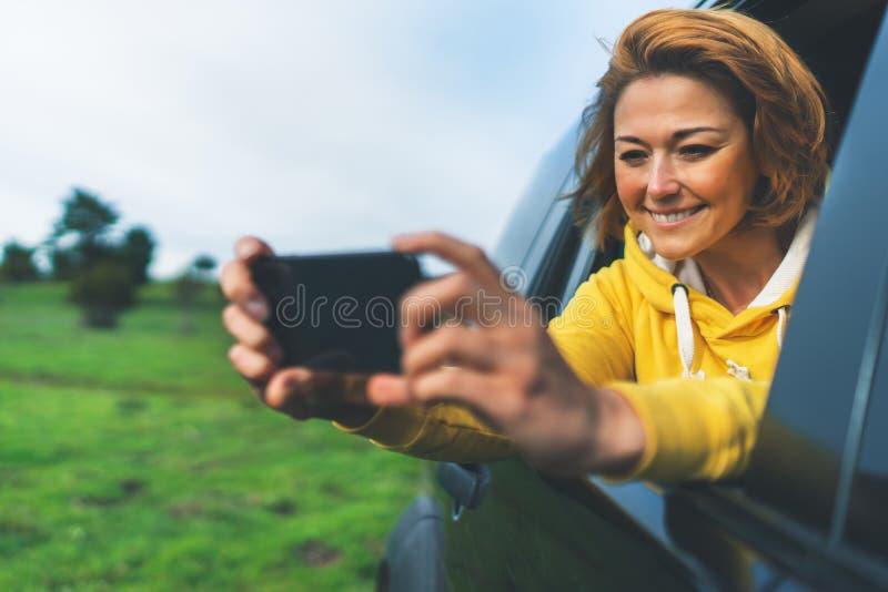 Fille de touristes de sourire dans une fenêtre ouverte d'une voiture automatique prenant le selfie de photo au téléphone intellig images libres de droits