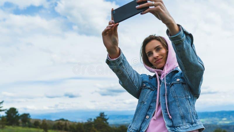 Fille de touristes sur des nuages de ciel bleu de fond prenant le selfie de photo au téléphone intelligent mobile, personne regar photos libres de droits