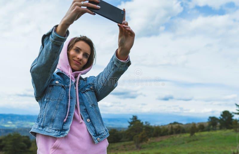 Fille de touristes sur des nuages de ciel bleu de fond prenant le selfie de photo au téléphone intelligent mobile, personne regar images stock