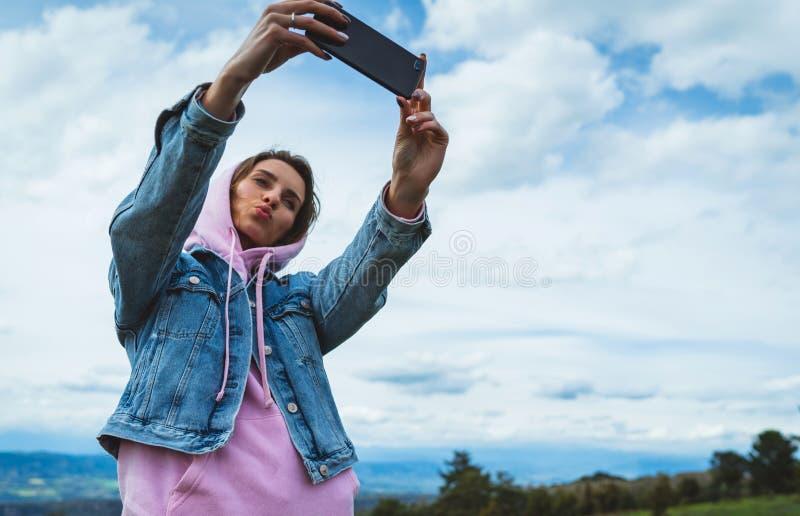 Fille de touristes sur des nuages de ciel bleu de fond prenant le selfie de photo au téléphone intelligent mobile, personne regar photo libre de droits