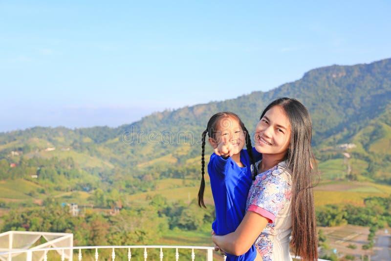Fille de transport de mère asiatique sur le balcon au flanc de coteau et à la caméra de pointage photos libres de droits