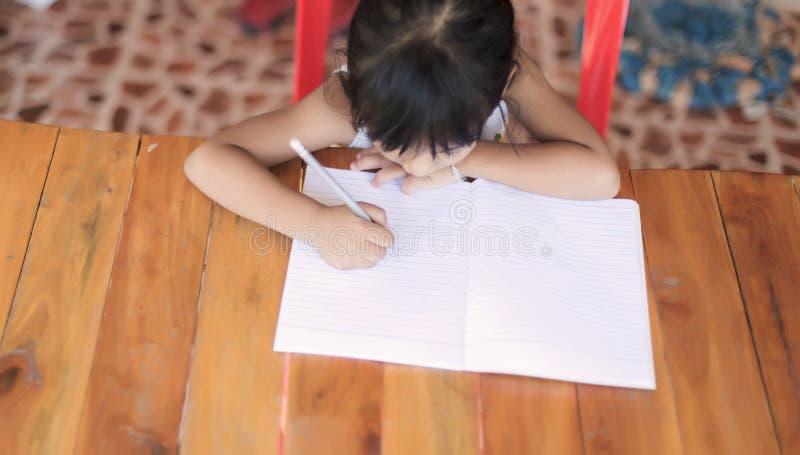 Fille de travail écrivant des photos d'un livre, des images et des photos d'actions photographie stock