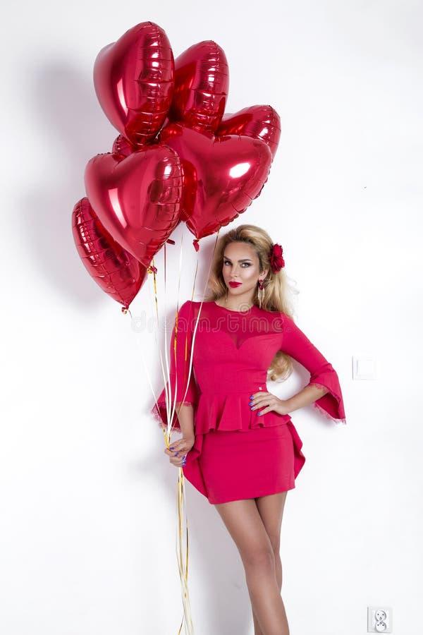 Fille de Valentine Beauty avec le ballon à air rouge sur le fond blanc Belle jeune femme heureuse présent des produits image stock
