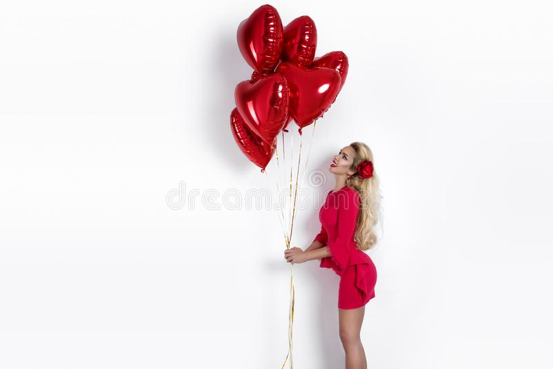 Fille de Valentine Beauty avec le ballon à air rouge sur le fond blanc Belle jeune femme heureuse présent des produits images stock