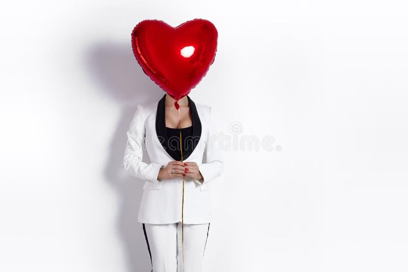 Fille de Valentine Beauty avec le portrait rouge de ballon à air, d'isolement sur le fond Belle jeune femme heureuse dans un smok photos libres de droits