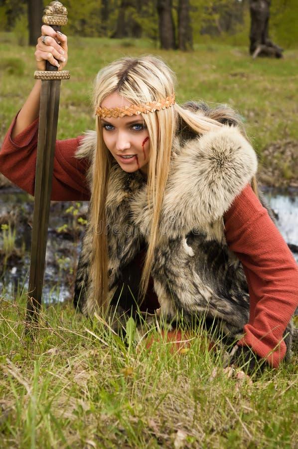 Fille de Viking avec l'épée dans un bois image stock