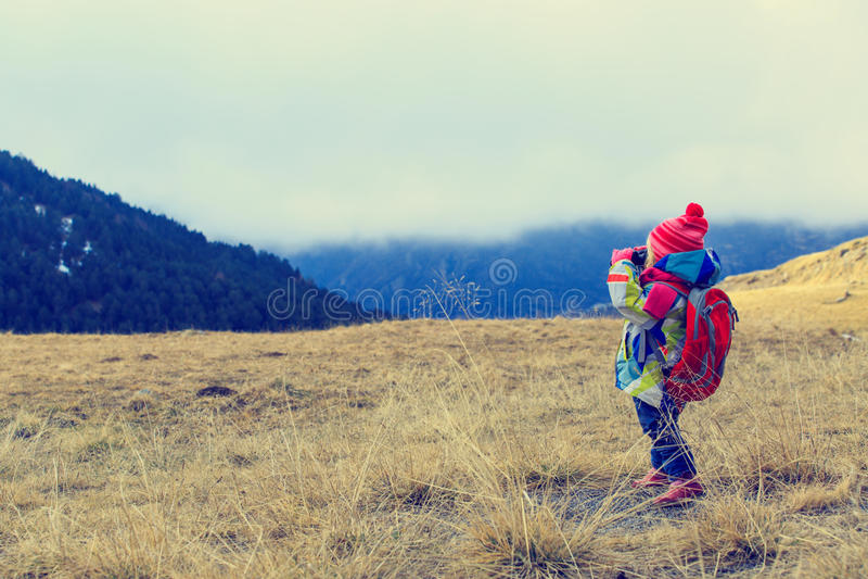 Fille de voyage de famille petite avec des jumelles explorant des montagnes d'hiver images libres de droits