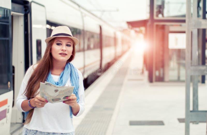 Fille de voyageur attendant et montant à bord d'un train sur la plate-forme ferroviaire photographie stock