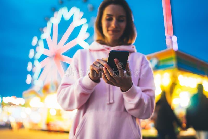 Fille de vue de face dirigeant le doigt sur le smartphone d'écran sur la lumière de bokeh de fond de defocus dans l'attraction de photographie stock
