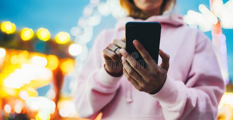 Fille de vue de face dirigeant le doigt sur le smartphone d'écran sur la lumière de bokeh de fond de defocus dans l'attraction de image stock