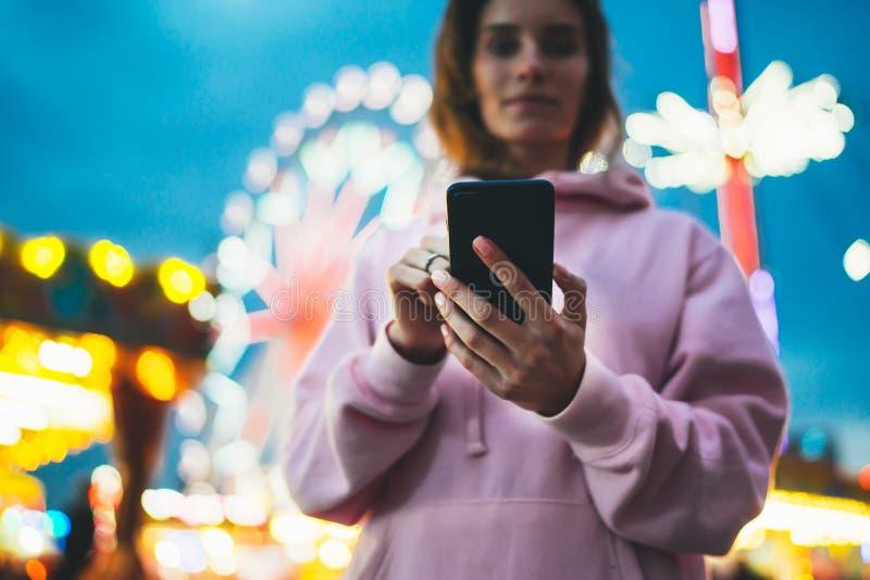 Fille de vue de face dirigeant le doigt sur le smartphone d'écran sur la lumière de bokeh de fond de defocus dans l'attraction de photographie stock libre de droits
