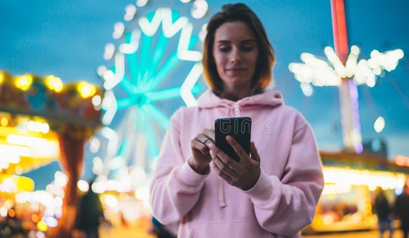 Fille de vue de face dirigeant le doigt sur le smartphone d'écran sur la lumière de bokeh de fond de defocus dans l'attraction de photos libres de droits