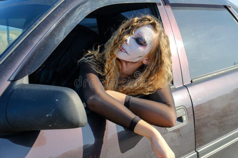 Fille de zombi avec des yeux au beurre noir et bouche ensanglantée dans la voiture image libre de droits