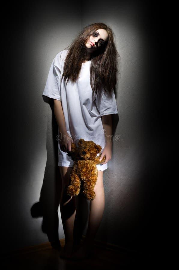Fille de zombi avec l'ours de nounours images stock