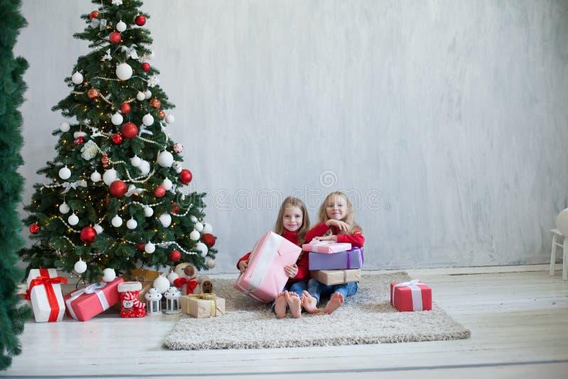 Fille des vacances deux de Noël avec l'arbre de Noël de nouvelle année de présents sur les cadeaux gris d'un fond photos libres de droits