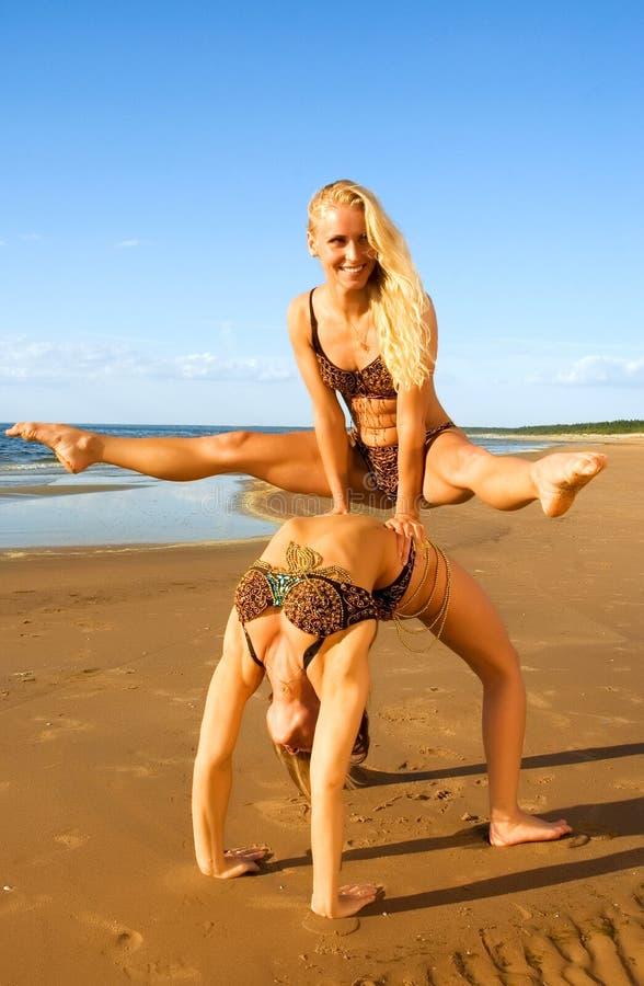 Fille deux acrobatique sur la plage images libres de droits