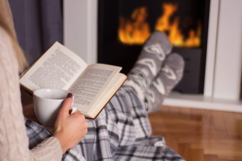 Fille devant le livre de lecture de cheminée et pieds de chauffage sur le feu images stock