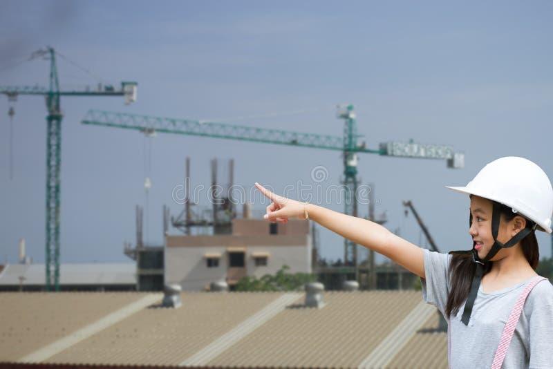 Fille dirigeant le doigt : Les ingénieurs de chapeau d'usage de fille se dirigent photographie stock libre de droits
