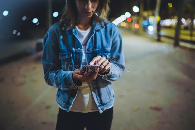 Fille dirigeant le doigt sur le smartphone d'écran sur la lumière de bokeh de lueur d'illumination de fond dans la ville atmosphé photographie stock