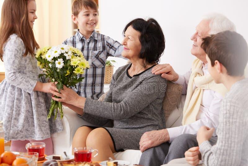 Fille donnant des fleurs à sa grand-maman images stock