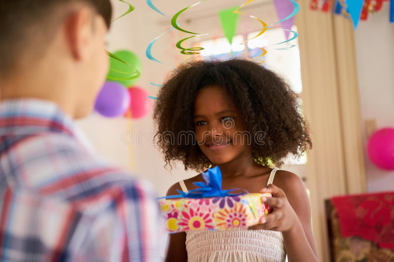 Fille donnant le cadeau d'anniversaire au camarade de classe de garçon images libres de droits