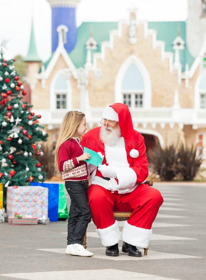 Fille donnant le list d'envie à Santa Claus photos stock