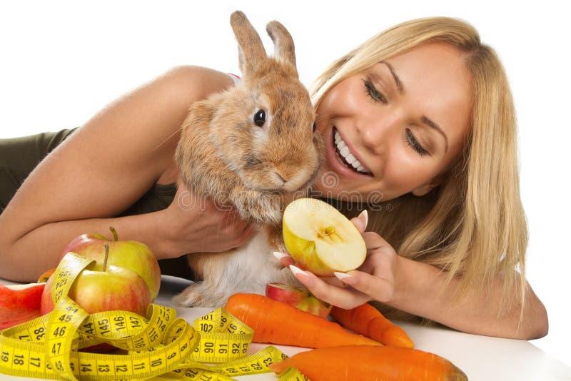 Fille donnant les légumes frais au lapin image libre de droits