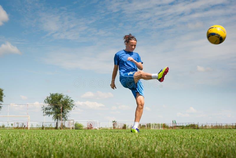 Fille donnant un coup de pied le ballon de football photo stock