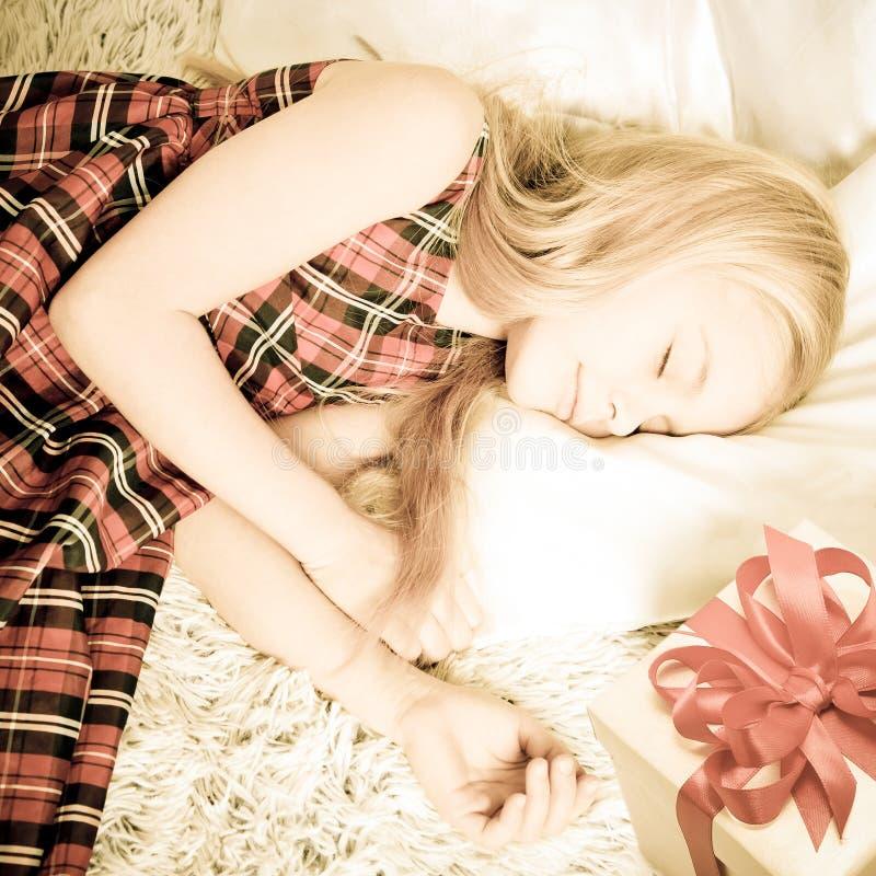Fille dormant avec le cadeau Rétro type image stock