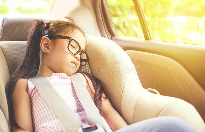 Fille dormant dans le siège de voiture d'enfant image libre de droits