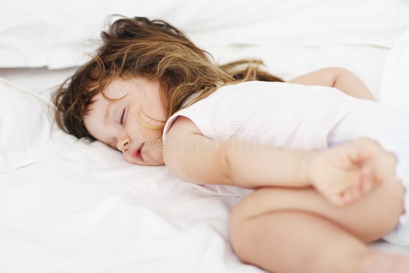 Fille dormant paisiblement dans un bâti photographie stock
