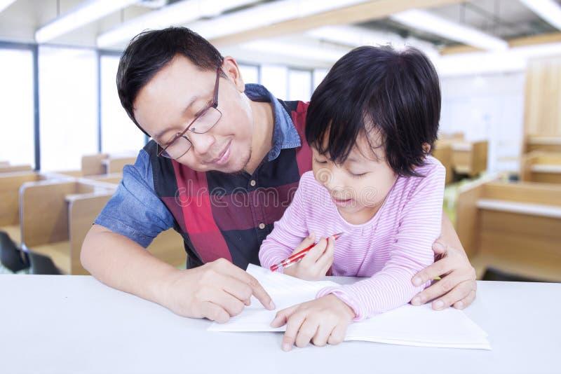 Fille douce apprenant dans la classe avec le professeur images libres de droits