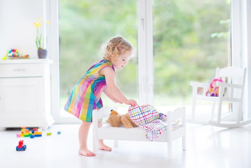 Fille douce d'enfant en bas âge jouant avec son ours de nounours image stock