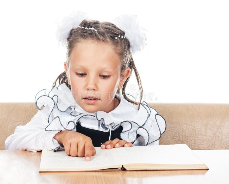 Fille douce dans l'uniforme scolaire lisant un livre image stock