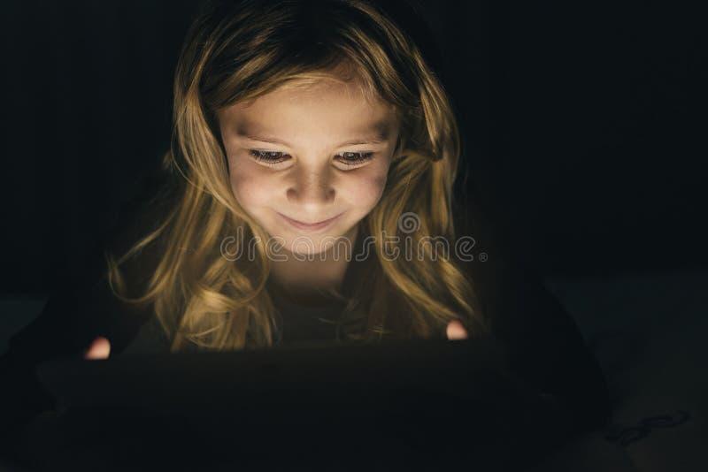 Fille douce de blondie jouant sur une Tablette image stock