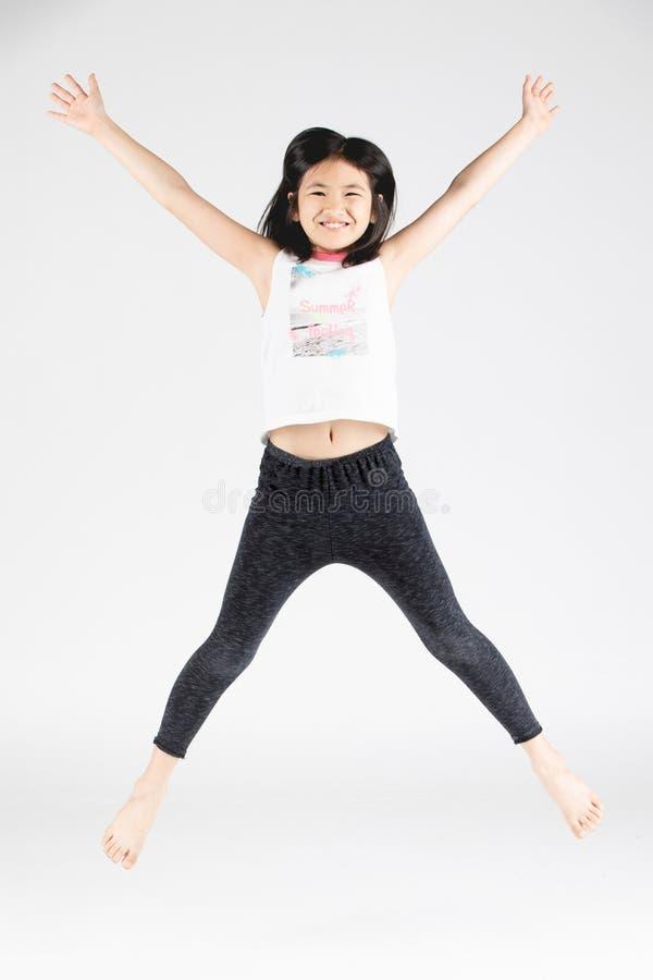 Fille drôle asiatique d'enfant sautant sur le fond gris photos stock