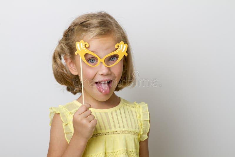 Fille drôle avec accessoires de papier enfant tenant des verres sur le bâton photographie stock libre de droits