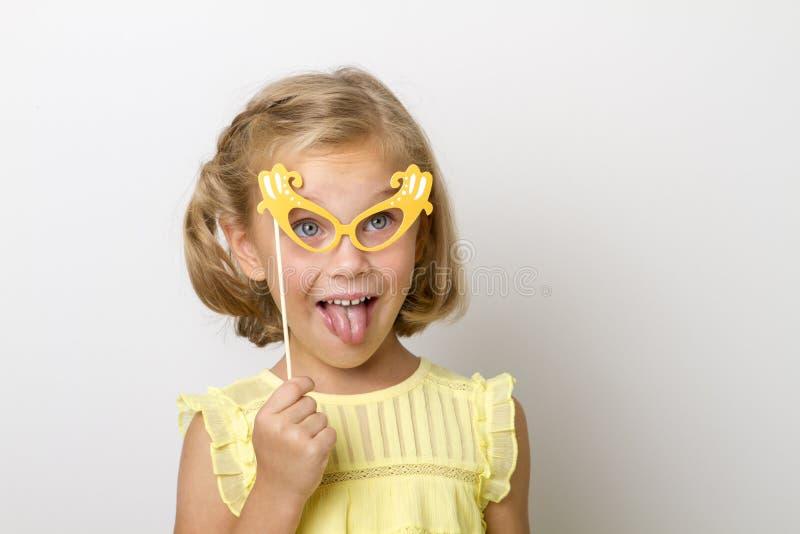 Fille drôle avec accessoires de papier enfant tenant des verres sur le bâton photo stock