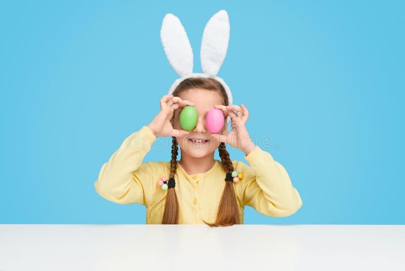 Fille drôle avec des oeufs de pâques près des yeux photo libre de droits