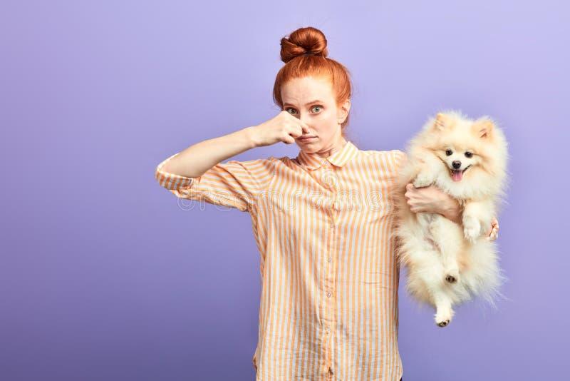 Fille drôle avec la chemise rayée élégante fermant son nez, comme le chien pète photographie stock