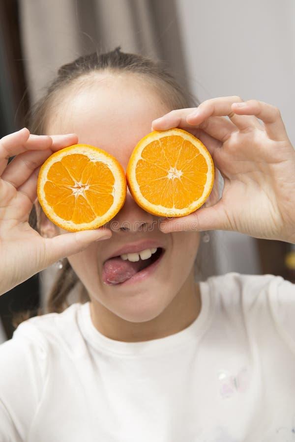 Fille drôle avec la demi orange photo stock