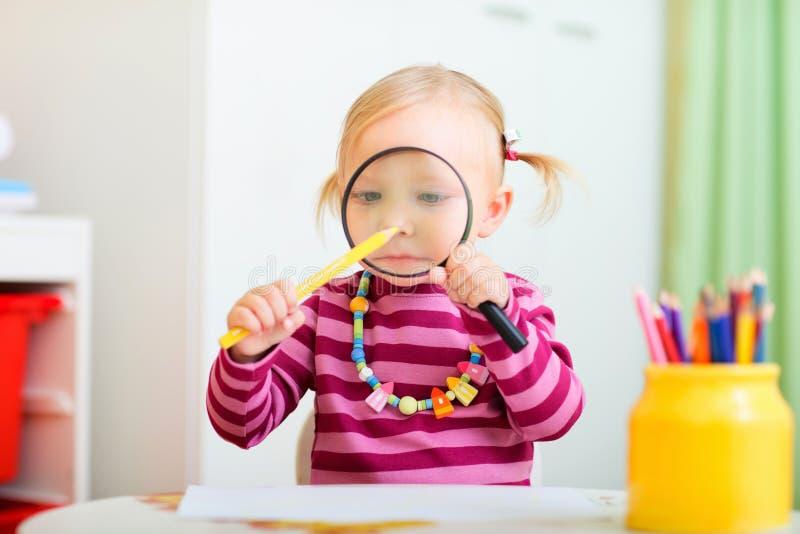 Fille drôle d'enfant en bas âge jouant avec la loupe photographie stock libre de droits