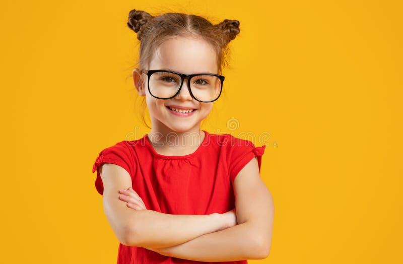 Fille drôle d'enfant en verres sur le fond coloré photo stock