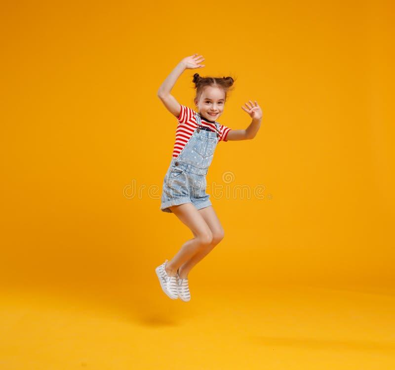 Fille drôle d'enfant sautant sur le fond jaune coloré photos stock
