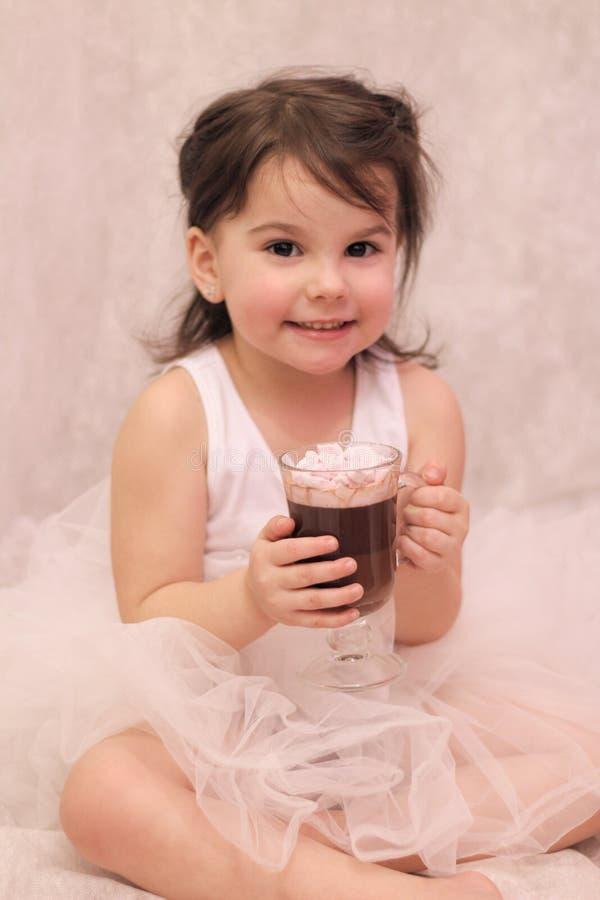 fille drôle dans le tutu de ballerine avec un verre de boisson chaude dans des ses mains photo stock