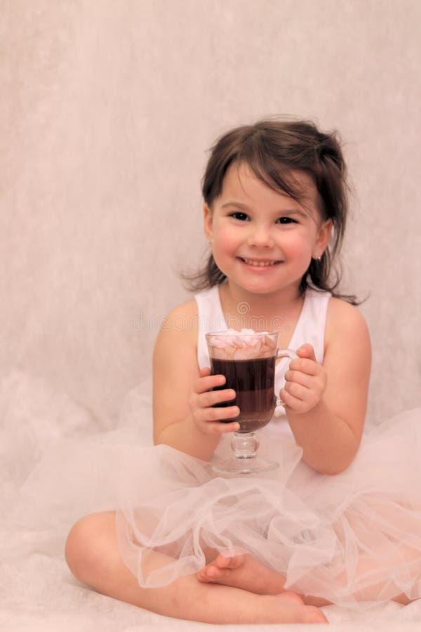 fille drôle dans le tutu de ballerine avec un verre de boisson chaude dans des ses mains image stock