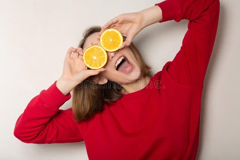 Fille drôle de brune posant avec une demi orange, couvrant des yeux d'orange contre le mur blanc images libres de droits