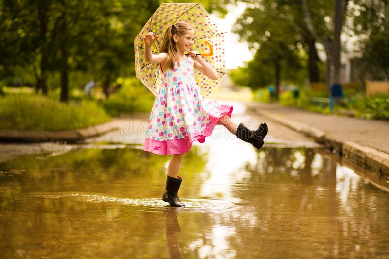 Fille drôle heureuse d'enfant avec le parapluie sautant sur des magmas dans des bottes en caoutchouc et dans la robe de point de  photo libre de droits
