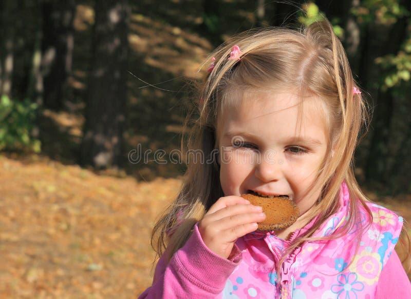 Fille drôle mangeant le biscuit photo stock