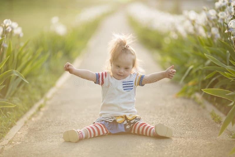 Fille drôle avec la trisomie 21 se reposant dans le soleil de coucher du soleil photo libre de droits